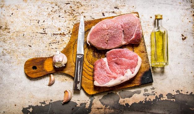 마늘과 기름 나무 보드에 원시 신선한 고기. 소박한 배경. 평면도