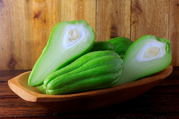Raw, fresh and organic chayote, whole and sliced in basket on rustic wooden table
