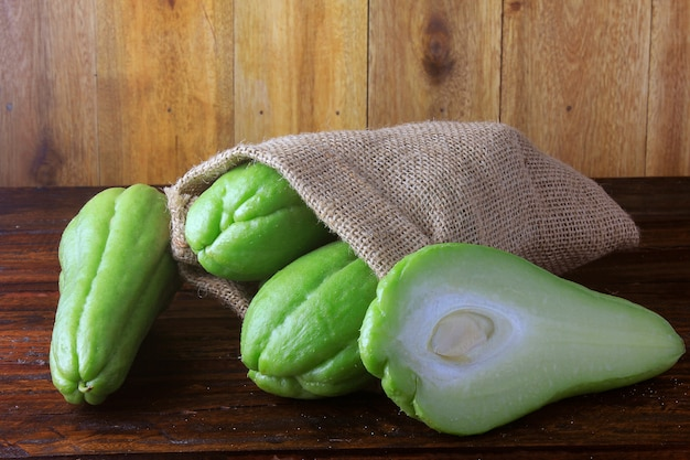 Raw, fresh and organic chayote, whole and sliced in rustic bag on wooden table
