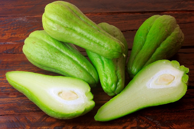 Raw, fresh and organic chayote, whole and sliced on rustic wooden table