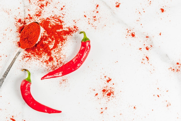 Raw fresh organic and dried ground chili pepper on white marble scene top view copy space