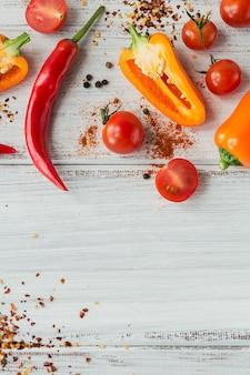 Сырые свежие органические смеси красочных перцев, помидоров черри и разных специй на белом деревянном столе