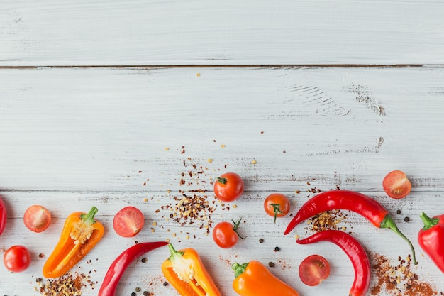 Raw fresh organic mix colorful peppers, cherry tomatoes and assorted spices on white wooden table