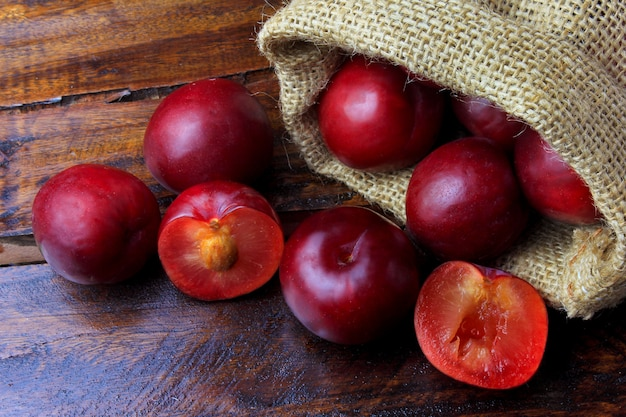 Raw and fresh organic plums inside rustic fabric bag on wooden table