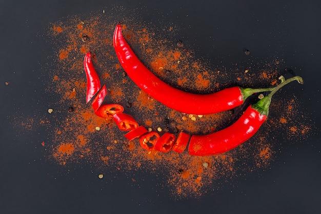 生の新鮮な有機赤唐辛子フレークとスライスした乾燥唐辛子。黒の背景に各種ペッパースパイス。食品の調味料。料理用の自家製スパイス材料。