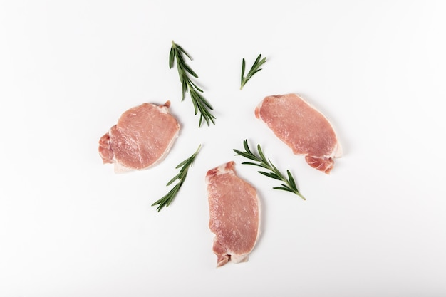 Raw fresh pork sliced meat with rosemary on  flat lay, top view