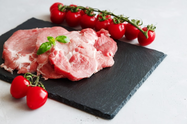 Raw fresh pork steaks with a sprig of basil and cherry tomatoes