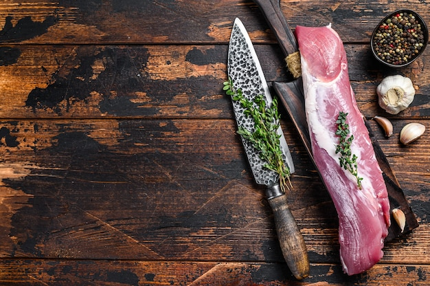 Raw fresh pork tenderloin meat on a cuuting board with cleaver. dark wooden background. top view. copy space.