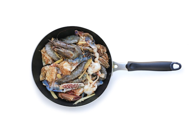 Raw fresh prawns and crab on frying pan isolated over background.