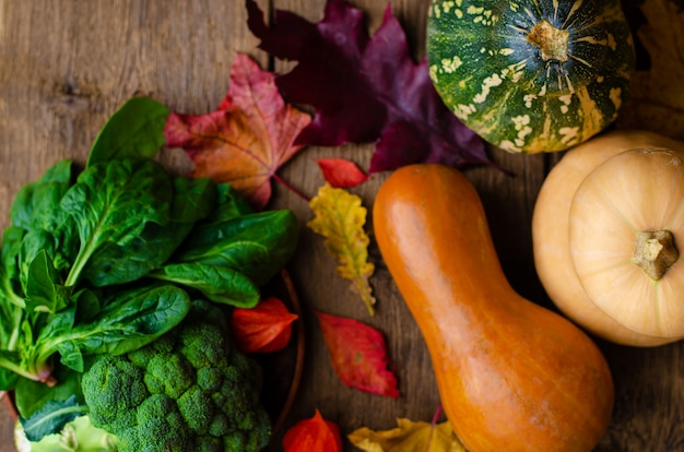 Raw fresh pumpkins, spinach and broccoli on wood
