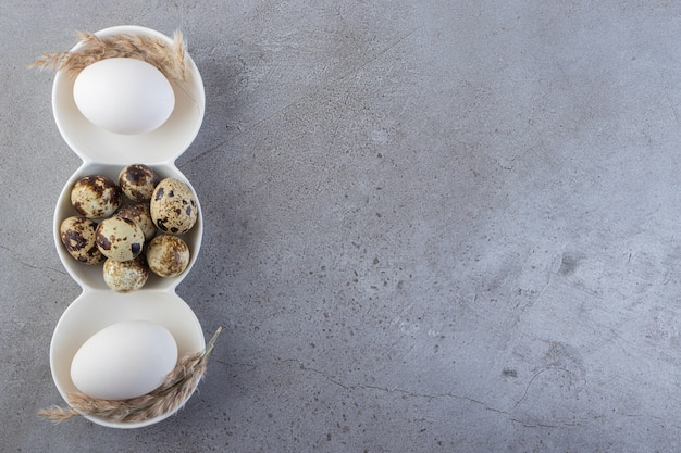 石の背景に置かれた生の新鮮なウズラの卵。