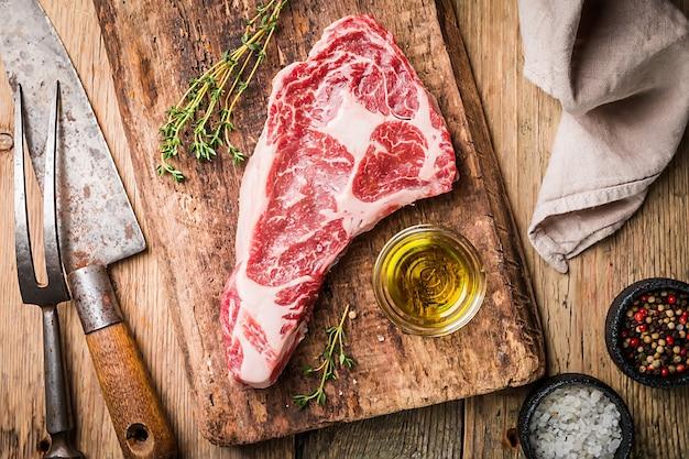 원시 신선한 ribeye 스테이크, 나무 표면에 조미료와 나이프와 포크가있는 쇠고기 고기, 평면도