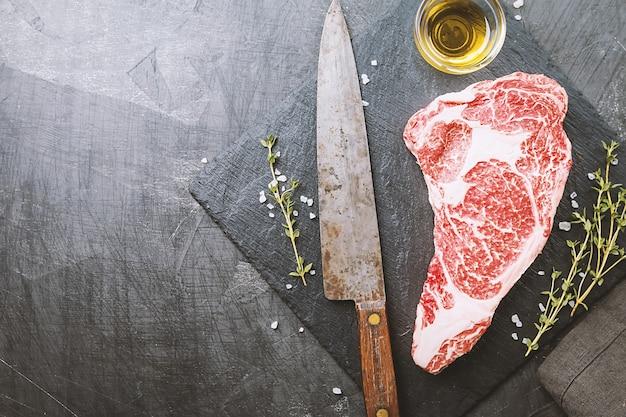 원시 신선한 ribeye 스테이크, 어두운 배경에 조미료를 곁들인 쇠고기 고기, 평면도