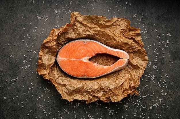 Сырой свежий стейк из лосося в пергаментной бумаге