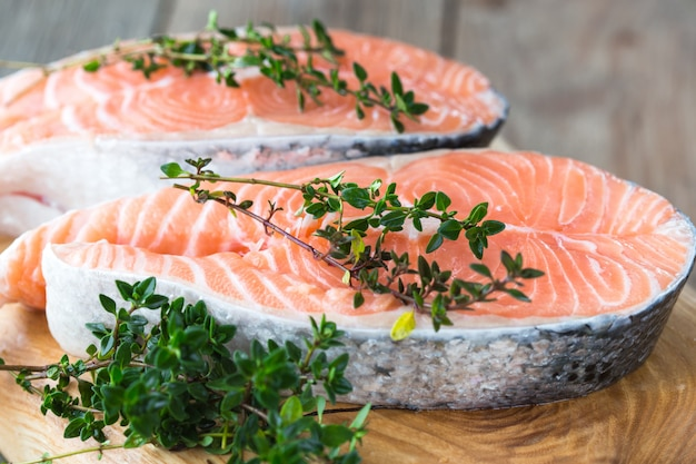 Raw, fresh salmon steak on a  board and spices around. raw salmon red fish. cooking salmon, seafood. healthy food concept. salmon and spices