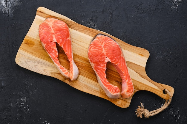 Raw fresh salmon steak on wooden cutting board
