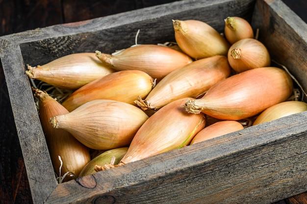 Сырые свежие луковицы лука-шалота луковицы в деревянной коробке рынка. темный деревянный фон. вид сверху.