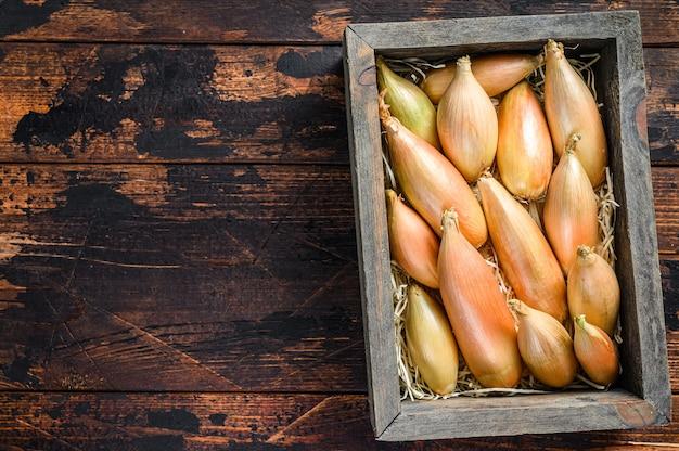 木製のマーケットボックスに生の新鮮なエシャロット玉ねぎの球根
