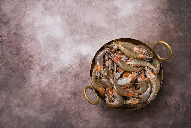 茶色のテーブルの上にヴィンテージ料理の生の新鮮なエビ。コピースペース、上面図