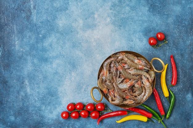 青いテーブルの上にヴィンテージ料理と野菜の生の新鮮なエビ。コピースペース、上面図。