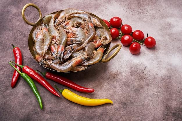 갈색 배경 위에 빈티지 접시에 원시 신선한 새우. 공간을 복사하십시오. 해산물 건강 식품 개념.