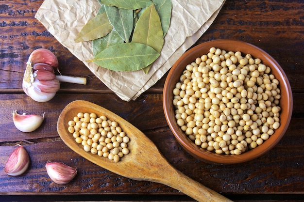 Raw and fresh soy beans inside white ceramic bowl on rustic wooden table
