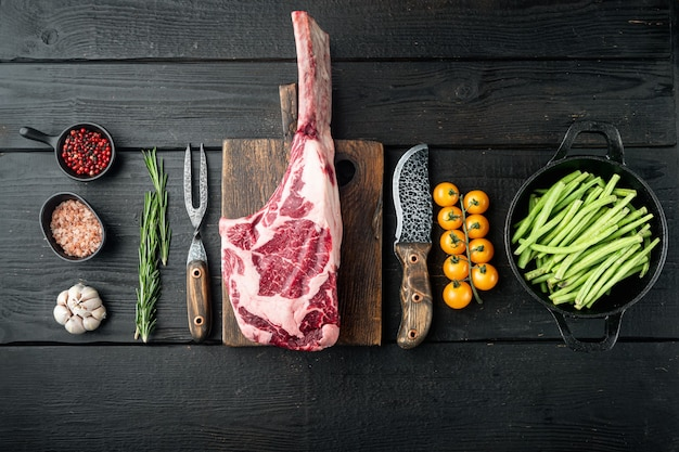 Raw fresh tomahawk dry aged marbled beef chop steak set, with grill ingredients, on black wooden table