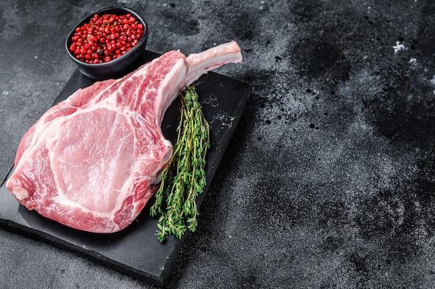 대리석 보드에 원시 신선한 토마 호크 돼지 고기 스테이크. 검정색 배경. 평면도. 공간을 복사하십시오.