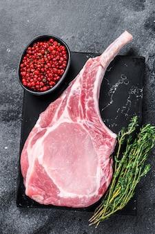 Сырой свежий стейк из свиной отбивной томагавк на мраморной доске