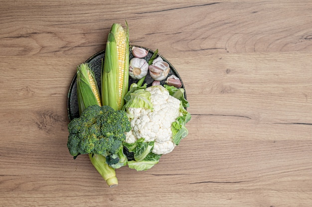 Raw fresh vegetables on a plate on a wooden table background top view.