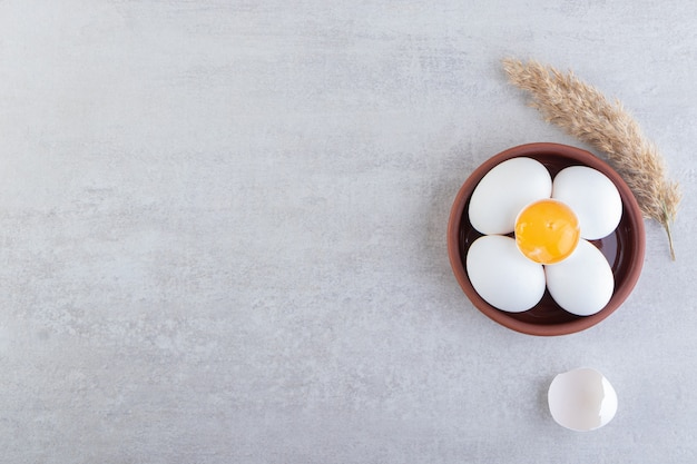 Сырые свежие белые куриные яйца на каменном фоне.