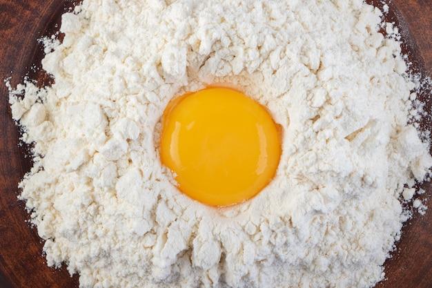 石の表面に生の新鮮な白い鶏の卵を置きます。