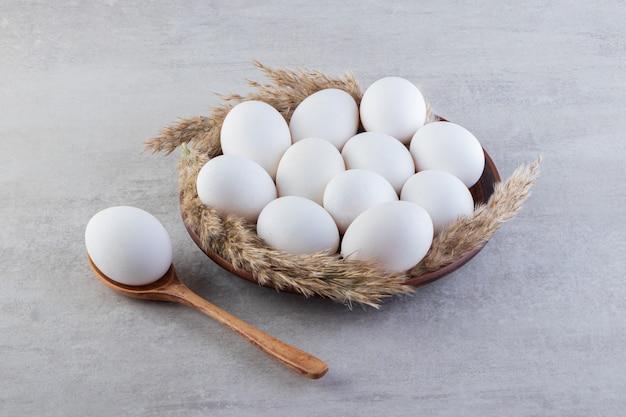 Сырые свежие белые куриные яйца на каменной поверхности.