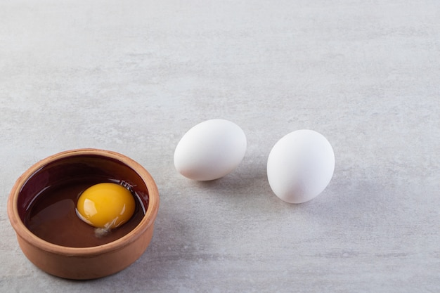 Raw fresh white chicken eggs placed on a stone surface.