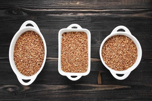 Raw fried buckwheat grains in white bowls, flat lay