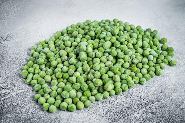Сырой замороженный зеленый горошек на кухонном столе
