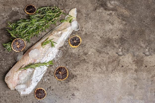 生冷凍メルルーサの切り身、氷、新鮮なローズマリー、ドライレモンスライス。