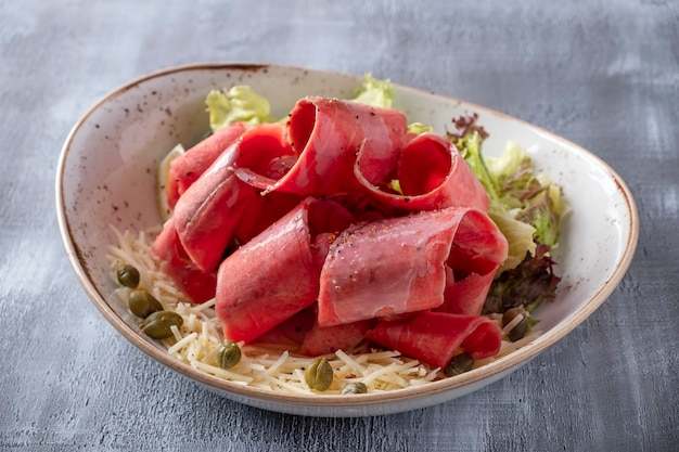 Raw frozen meat with cheese, capers and lemon