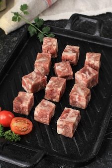 스파이스 및 야채를 곁들인 블랙 스테이크 플레이트에 냉동 사이코로 와규 원시 또는 주사위 쇠고기 스테이크