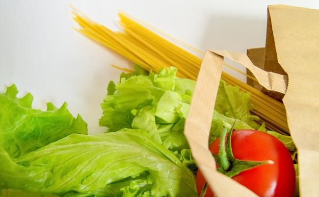 生の果物と野菜、白い壁に紙袋からロールアウトしたパスタ、ショッピングのコンセプト、出前