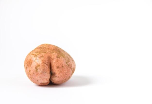 白い背景の上のお尻の形で生の面白いジャガイモ。