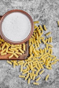 大理石のテーブルに生のフジッリと小麦粉の入ったボウル。