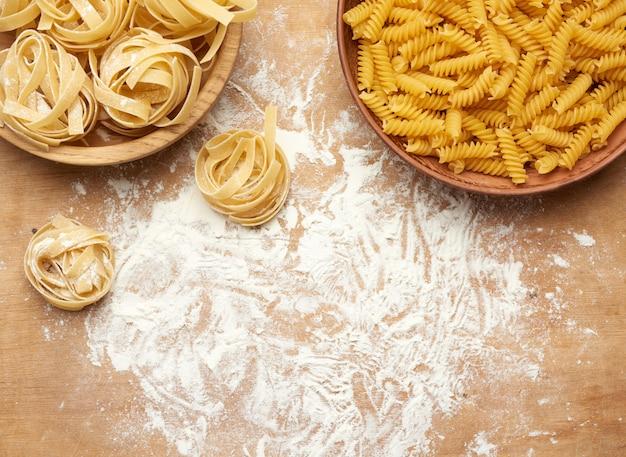Сырые фузилли и феттучини макароны в деревянные тарелки на коричневый деревянный стол