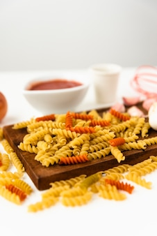 Raw fusilli pasta and ingredient with wooden cutting board on white background