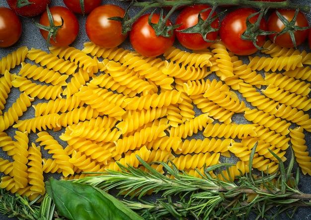 Сырые макароны фузилли с помидорами, зеленью и базиликом. итальянская паста с ингредиентами цветов итальянского флага