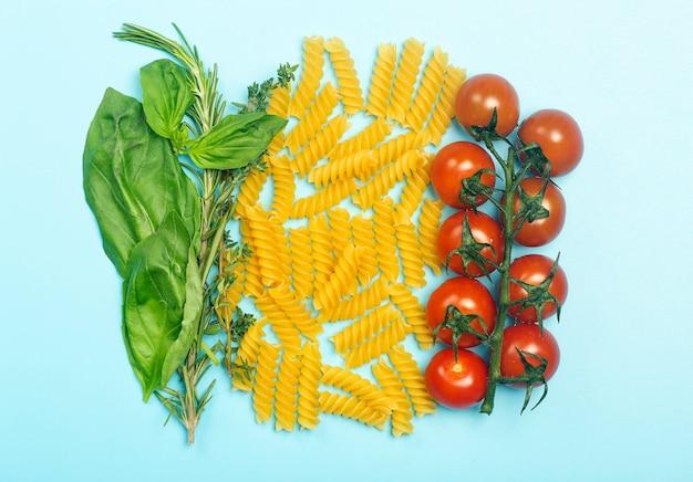 Сырые макароны фузилли с помидорами, зеленью и базиликом.
