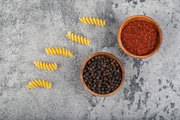 Сырые макароны фузилли с различными перцами на камне.