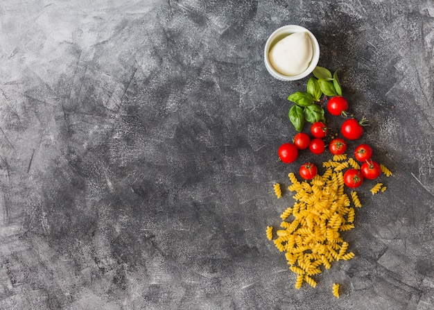 Raw fusilli with cherry tomatoes; basil leaves; black pepper and cheese on texture background