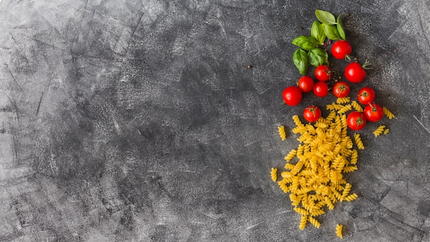 Raw fusilli with cherry tomatoes and basil leaves on texture background