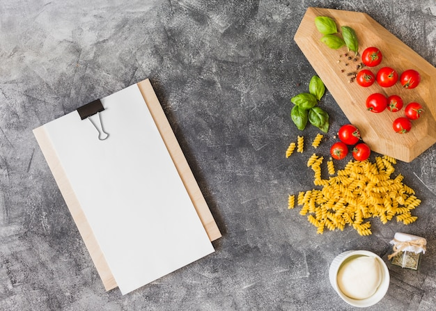 Raw fusilli with ingredients and blank paper on clipboard over the grunge background